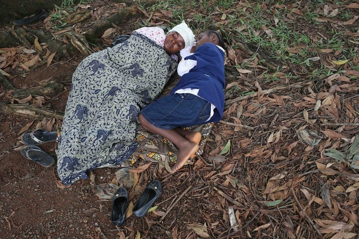 A woman and her daughter wait for one of few beds at an Ebola treatment center.