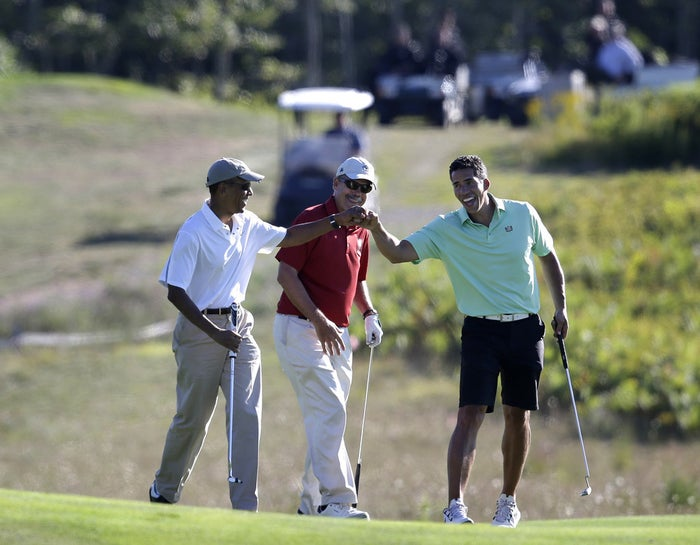 President Obama bumps fists with Cy Walker while golfing on Martha's Vineyard Wednesday.