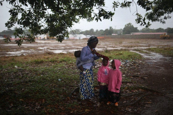 A woman and her children wait outside a new Ebola treatment center run by Doctors Without Borders.