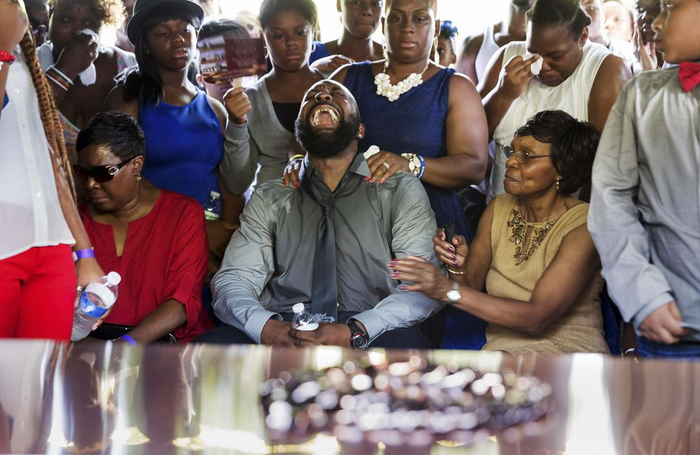 Michael Brown Sr. yells out as the casket is lowered during the funeral service for his son Michael Brown in Normandy, Missouri, Monday, Aug. 25.