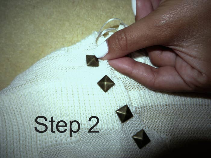 Step 2: Poke the stud through the object you chose. Note: Most sweaters are thin enough that the stud should just poke through but for thicker objects use a safety pin to poke a hole where the prongs will go through.
