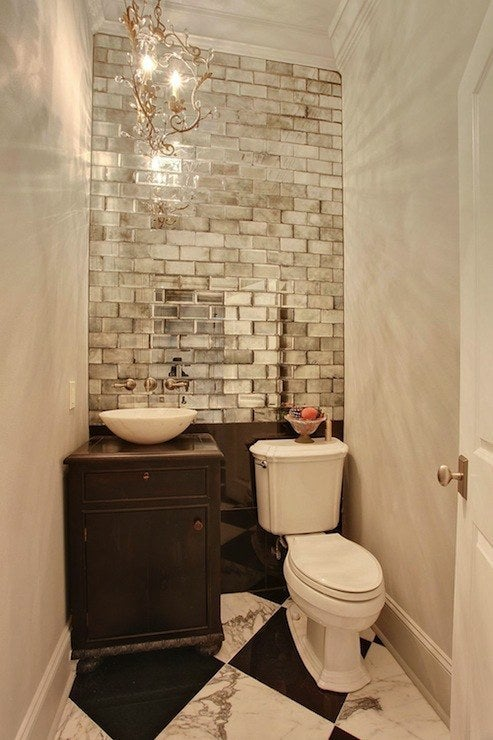 Mirrors can instantly double the appearance of a room, but there's no reason you have to go the traditional route! Metallic subway tile adds a layer of texture to this tiny WC.