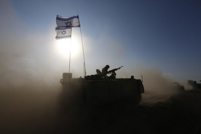 An Israeli soldier rides an armored personnel carrier near Gaza.