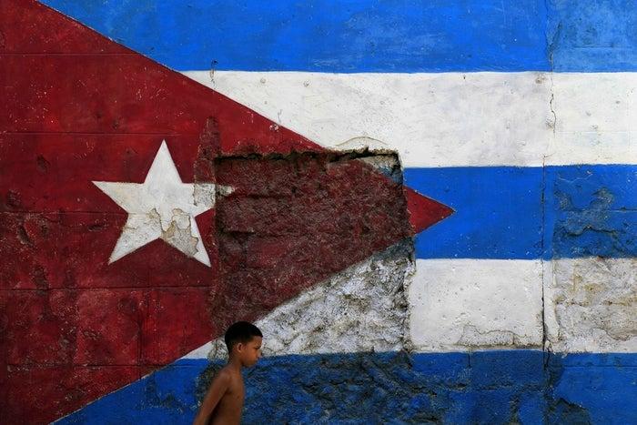 A child walks by a Cuban flag in Havana.