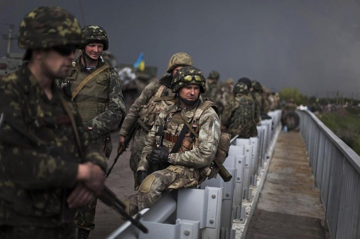 Ukrainian Army soldiers are seen atop of a bridge while pro-Russia civilians block the road in the village of Andreevka, 10 km south of Slavyansk in Ukraine in May.