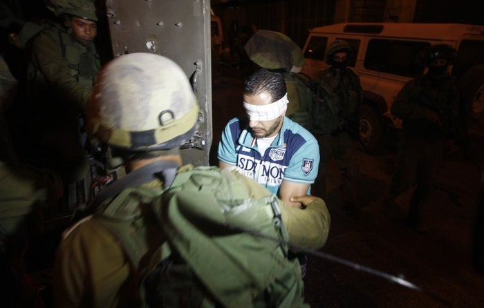 Israeli soldiers detain a blindfolded Palestinian in the West Bank City of Hebron, July 2, 2014.
