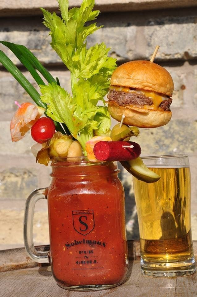 """According to the bar's website, the """"Bloody Masterpiece"""" involves 13 garnishes. The one that probably *stands out* would be...the pickle?JUST KIDDING, it would be the bacon cheeseburger."""