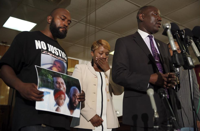 Lesley McSpadden and Michael Brown Sr., the parents of Michael Brown, listen as attorney Benjamin Crump speaks during a news conference in Jennings, Missouri.