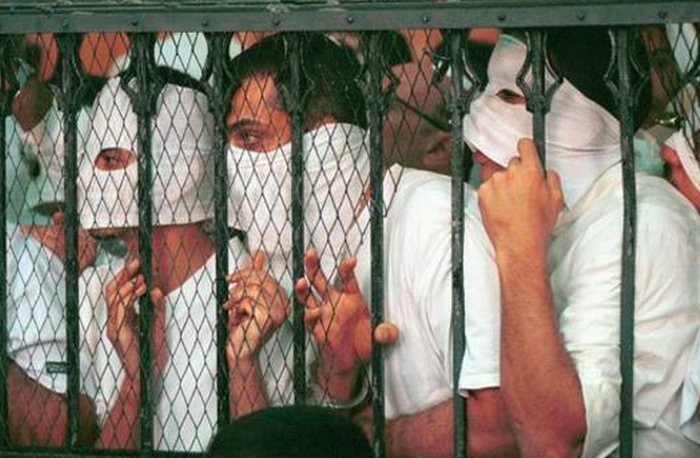 Defendants in a courtroom cage during the 2001 Queen Boat trial, at which more than 50 men were accused of homosexuality.