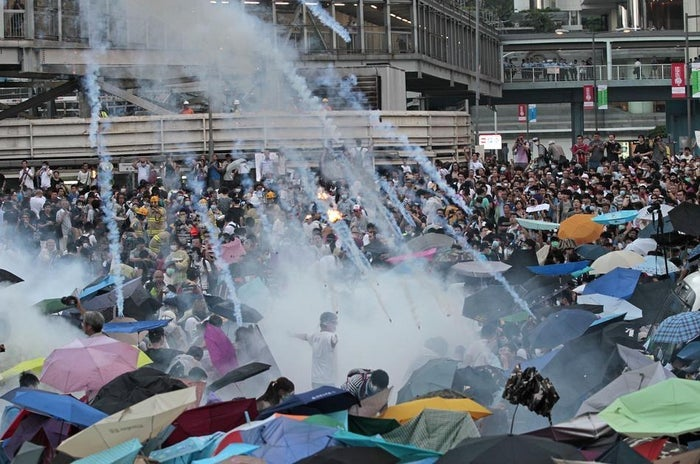 Riot police launch tear gas into the crowd as protesters surround the government headquarters in Hong Kong on Sept. 28.