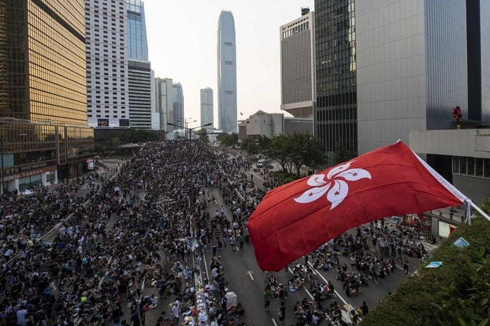 A protester waves a Hong Kong flag during a rally as they block the main road to the financial Central district in Hong Kong on Sept. 29.