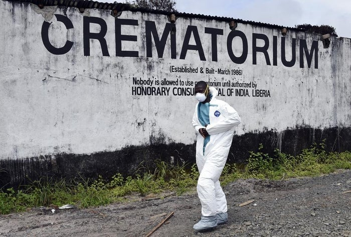 A medical worker walks past the crematorium where victims of Ebola are burned in Monrovia, Liberia, on Sept. 29.