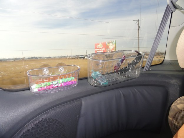 Shower caddies attached to a van windshield holding art and entertainment supplies for kids