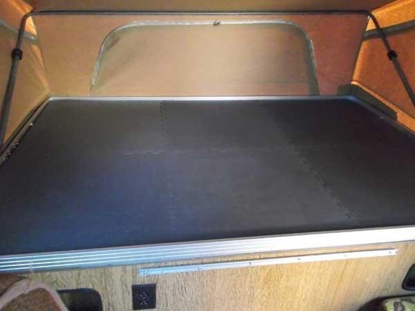 Rubber floor mat attached to the bottom of a bunk in a van or RV