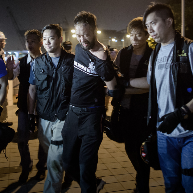 Protester Ken Tsang being led off by police officers before being beaten.