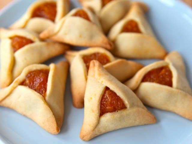Hamantaschen, known as oreilles d'aman to French speakers, are triangular, jelly-filled cookies Jews make for the holiday of Purim. They are made to resemble the hat or ears of Haman, the villain of the Purim story who tried and failed to destroy every last Jew in Persia. The holiday is celebrated by putting on costumes, drinking, and eating these cookies. Making hamantaschen is easy and super kid-friendly. Make the dough with a standard recipe and fill the cookies with anything from traditional poppy seeds to apricot jam to chocolate. Or, if you're feeling really ambitious, try something wild like a Girl Scout cookie-inspired version or a savory Mediterranean 'tasch. Lots more ideas here.