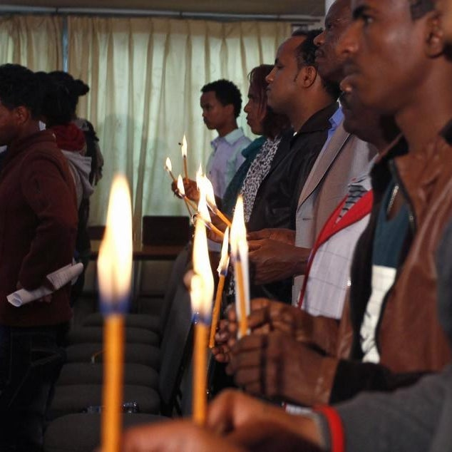 Eritrean people hold candles during a memorial gathering to mark the first anniversary of the Lampedusa migrant shipwreck.