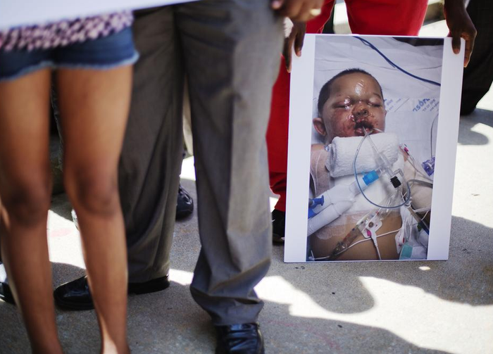 A photo of 19-month-old Bounkham Phonesavanh, who was severely burned by a flash grenade during a SWAT drug raid, is held by a supporter during a vigil outside Grady Memorial Hospital in Atlanta where he is undergoing treatment on June 2.
