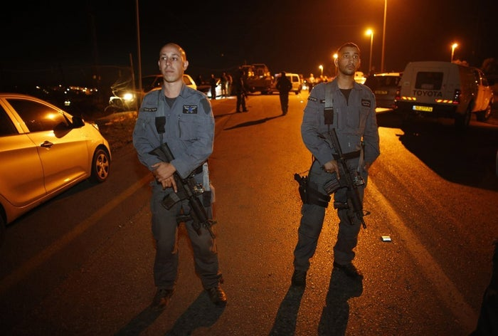 Israeli police officers stand guard at the scene of an attack in the West Bank.