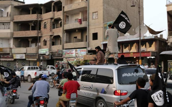 Men loyal to ISIS wave ISIS flags as they drive around Raqqa, Syria, in June 2014.