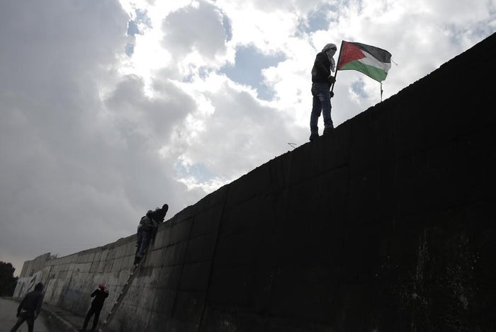 A Palestinian protester holds a national flag as he stands on top of Israel's controversial barrier that separates the West Bank town of Abu Dis from Jerusalem on November 17.