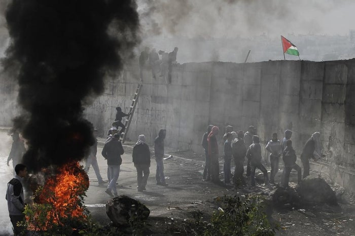 Palestinian protesters burn tyres while one of them tries to hammer a hole through Israel's controversial barrier that separates the West Bank town of Abu Dis (L) from Jerusalem on November 17.