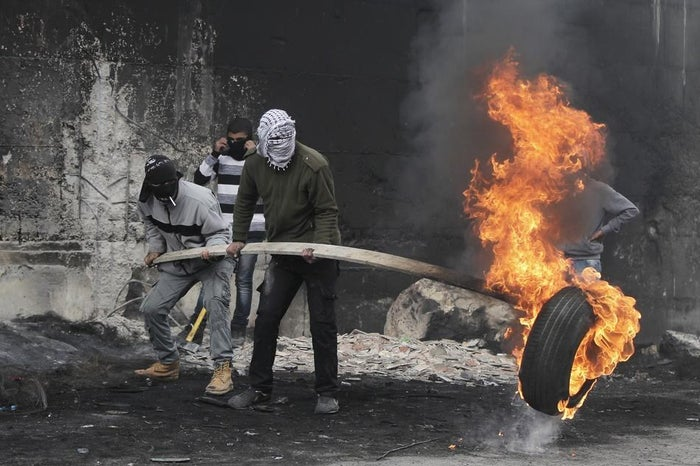 Palestinian protesters burn a tyre in front of the barrier that separates the West Bank town of Abu Dis from Jerusalem on November 17.