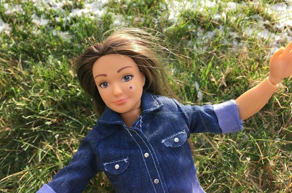 Una muñeca Lammily con una pegatina de un lunar