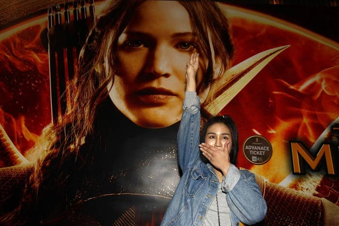 Thai student Natchacha Kongudom flashes a three-finger salute inspired by The Hunger Games in front of a billboard of the film outside the Siam Paragon cinema in Bangkok, on Nov. 20.