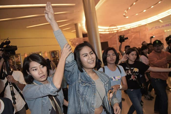 A Thai student flashes a three-finger salute, an unofficial symbol of resistance against the army's May coup, as she is escorted out of a cinema hall by plainclothes female police officers in Bangkok on Nov. 20.
