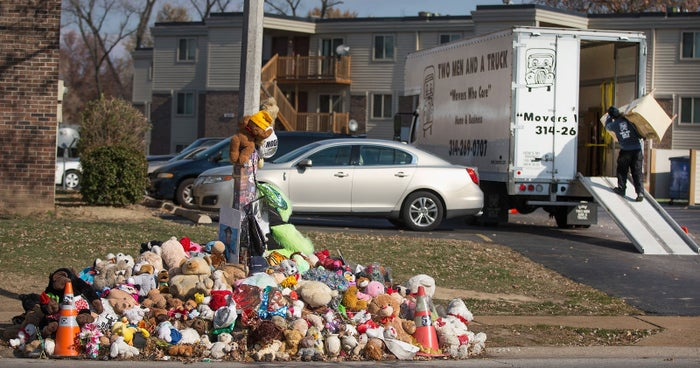 A moving crew helps a Canfield Green resident move from an apartment near the memorial for Michael Brown on November 19, 2014.