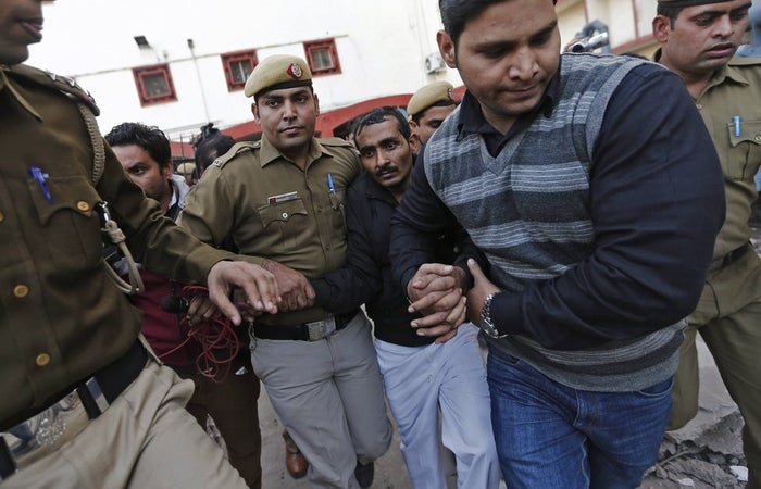 Police on Dec. 8 escort driver Shiv Kumar Yadav (center, in the black jacket) who is accused of raping his Uber passenger.