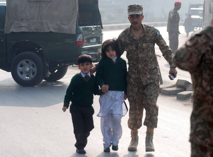 A soldier escorts schoolchildren after they were rescued.