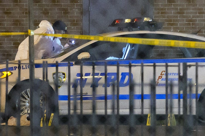 A police officer wipes tears from his face as he walks away from the scene the shooting Saturday.