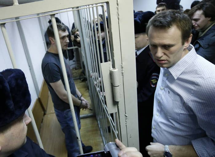 The Navalny brothers: Oleg in the cage; Alexey standing beside it.