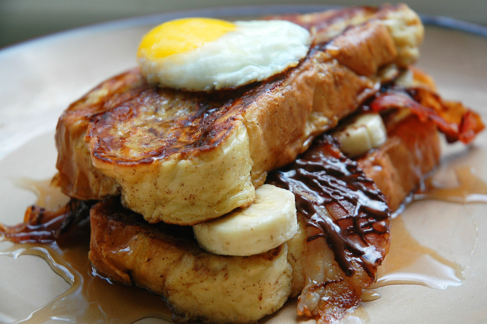 Chocolate-covered bacon and bananas between challah French toast with a fried egg on top. AKA A REASON TO LIVE. Get the recipe.