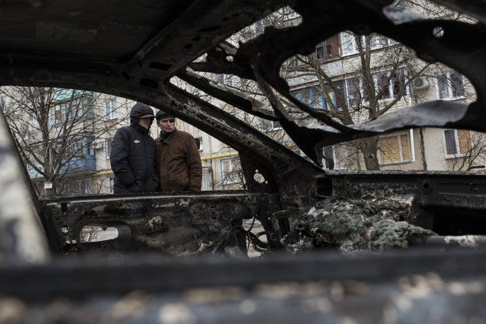 Local residents look at a burned car outside an apartment building in the Vostochniy district of Mariupol on Sunday, Jan. 25, 2015.