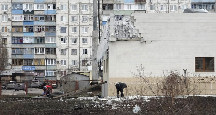 People remove debris near a building damaged by shelling on Saturday in Mariupol on Jan. 25, 2015.