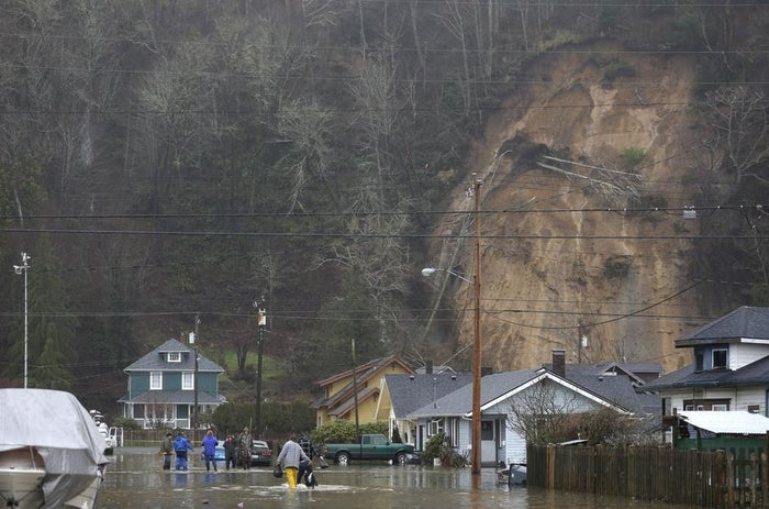 People walk along a flooded street near a landslide that caused the evacuation of several homes, Jan. 5, 2015, in Hoquiam, Wash.