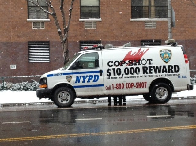 An NYPD van announced a $10,000 reward for information on the suspects who shot two NYPD officers in the Bronx.