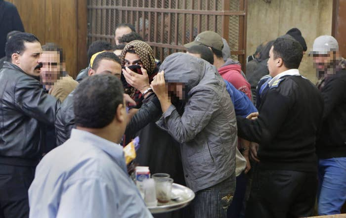 Men who were arrested by police looking for gays at a Cairo public bathhouse hide their faces after being acquitted.