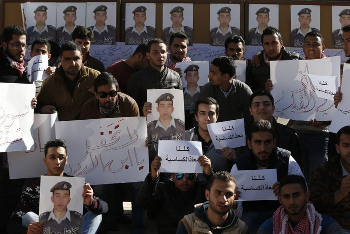 """Jordanians hold photos of Kasaesbeh and signs which read, """"We are all Muath."""""""