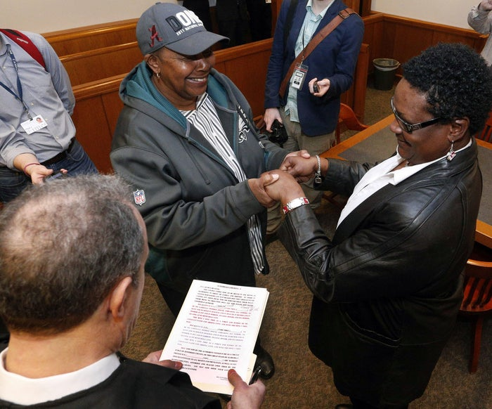 Circuit Judge Michael Graffeo, foreground left, marries Olanda Smith, center, and Dinah McCaryer, Monday, Feb. 9, 2015, at the Jefferson county courthouse in Birmingham, Ala.