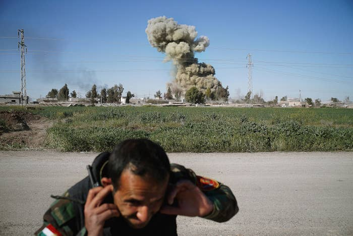 A peshmerga fighter covers his ears after a Kurdish explosive ordnance disposal (EOD) team detonates a car filled with explosives following the capture of the northern Iraqi town of Mullah Abdullah from ISIS militants.