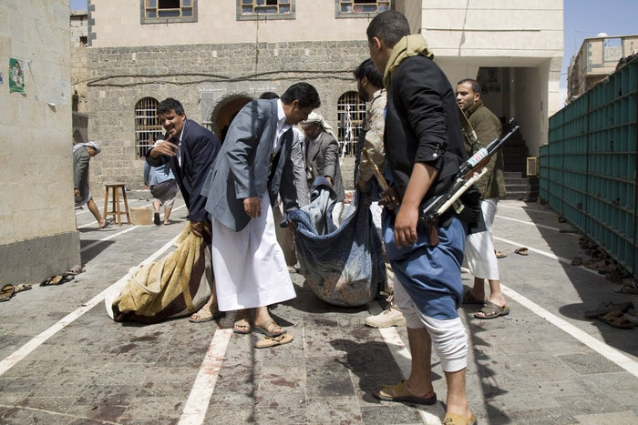 Houthi fighters carry the body of a man killed in a suicide attack at a mosque in Sanaa on Friday.