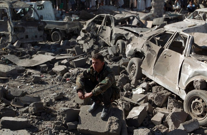 A Yemeni man wearing a military fatigue sits above debris at the site of a Saudi airstrike against Huthi rebels near Sanaa Airport.