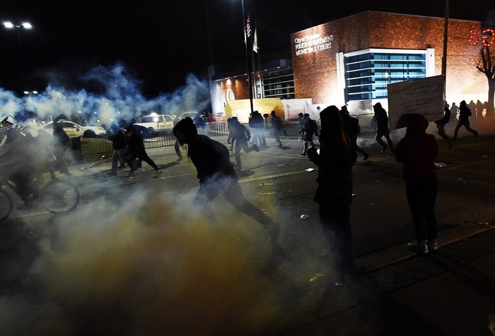 Demonstrators flee as police fire tear gas during clashes following the grand jury decision in the death of 18-year-old Michael Brown in Ferguson, Missouri, on Nov. 24, 2014.