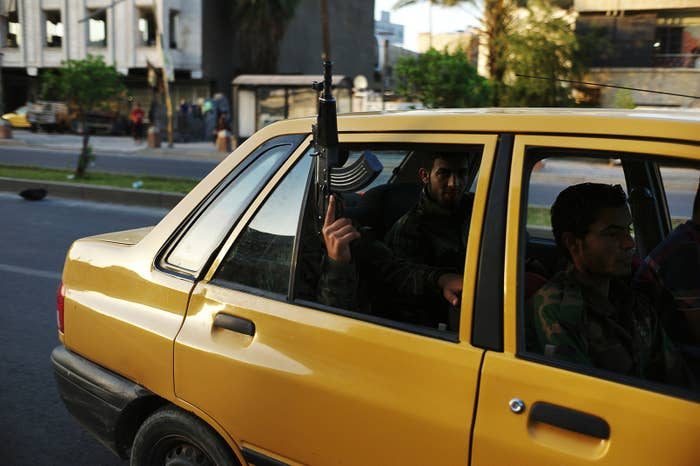 A Shiite militia fighter holds a weapon outside of the window of a Baghdad taxi on June 16, 2014.