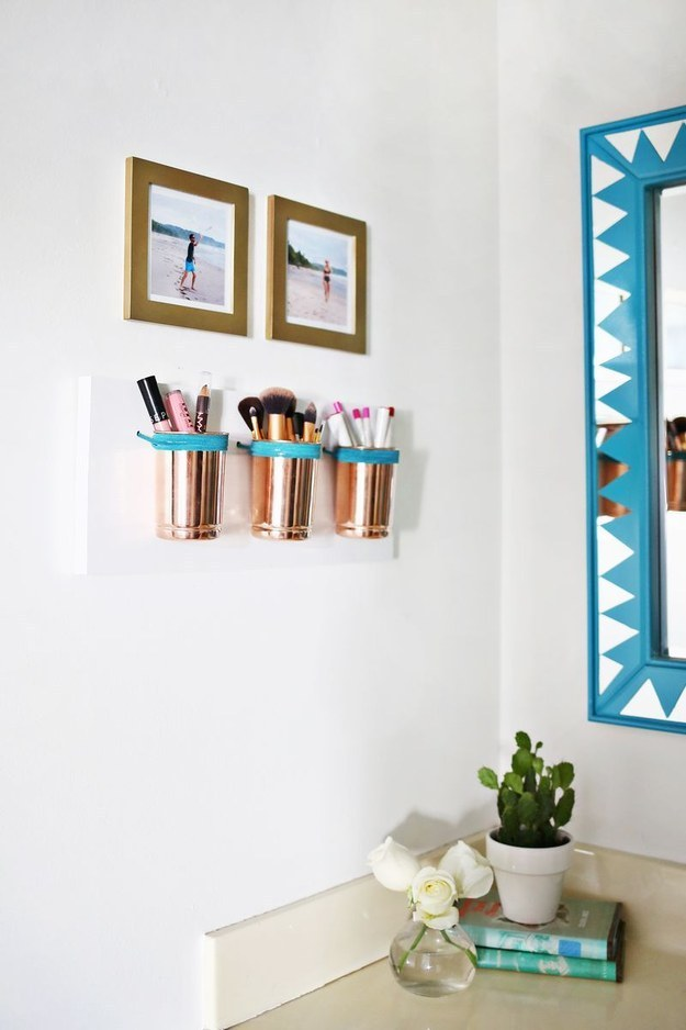 For a tiny bathroom, combine wall decorations with storage by making pretty copper makeup cups.