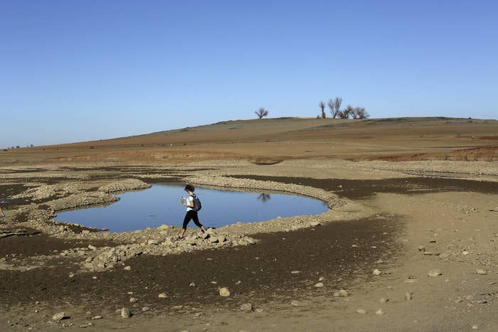 A visitor walks near the receding waters at Folsom Lake in January.